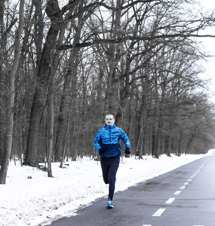 Man running on track near winter forest in the morning Stock Photo