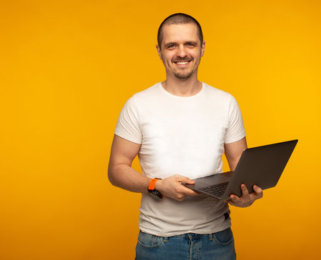 Freelancer man in white shirt holding laptop and smiling