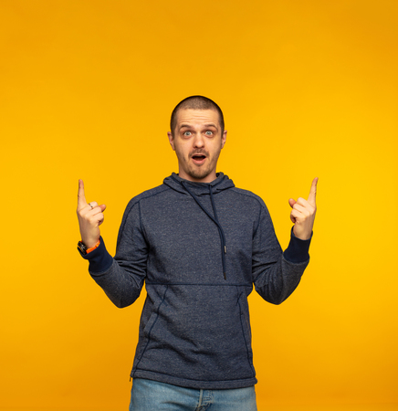 Surprised man pointing by hands up and looking in camera