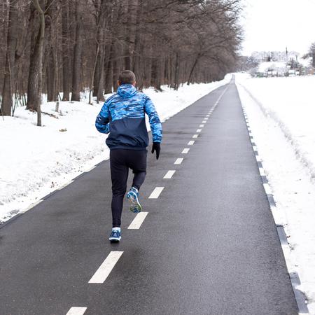 Man runner running on track in winter time