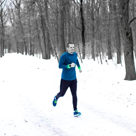 Adult man runner running in the forest in winter