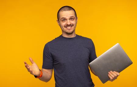 Surprised man freelancer or developer holding laptop and smiling
