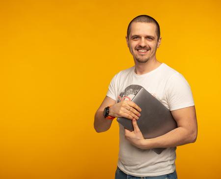 Developer or freelancer man holding laptop and smiling Stock Photo