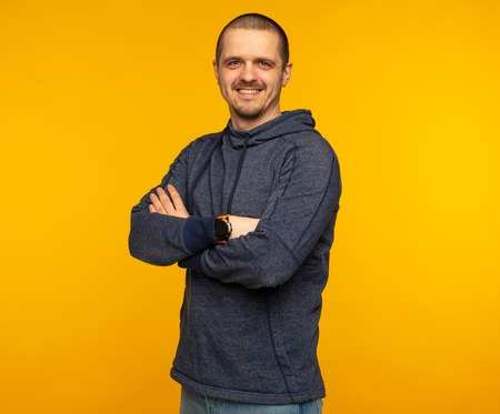 Man in hoodie with crossed arms smiling and looking in camera
