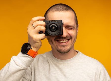 Photographer man holding camera near face and smiling
