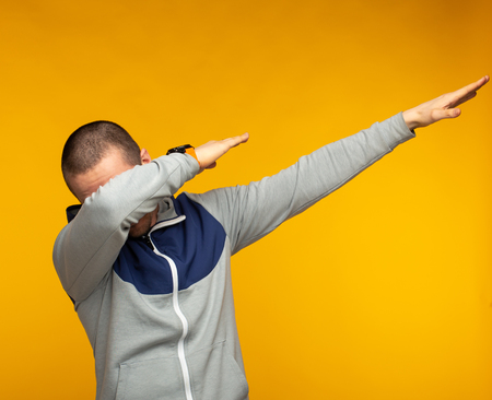 Man in hoodie show swag standing at orange background Stock Photo