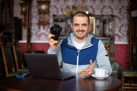 Man blogger holding camera in hand and telling something Stock Photo