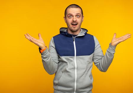 Surprised man in hoodie at orange background