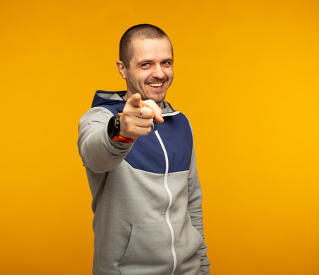 Man in casual wear pointing in camera and smiling