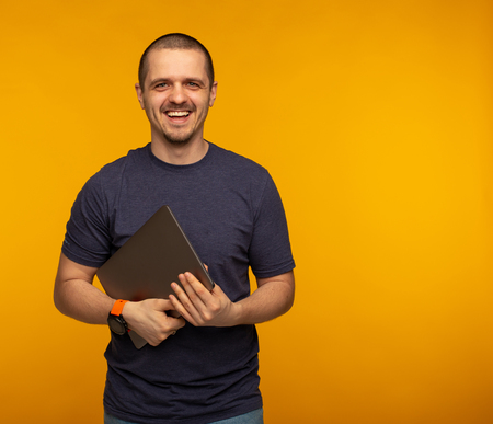 Freelancer or developer laughting and holding laptop Stock Photo