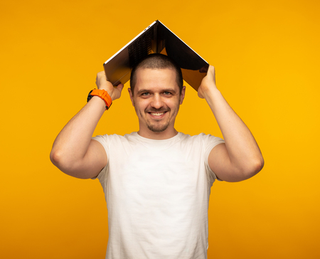 Man freelancer or IT programmer holding laptop over his head