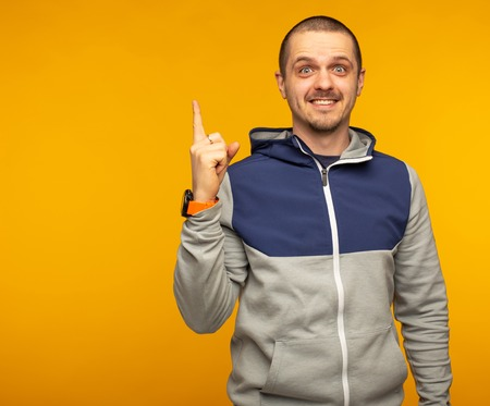 Smiling man pointing by hand and looking in camera Stock Photo