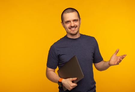 Startuper man freelancer or developer smiling and holding laptop