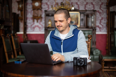 Man freelancer with laptop and camera working Stock Photo