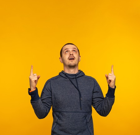 Surprised man in hoodie looking up and pointing by hands