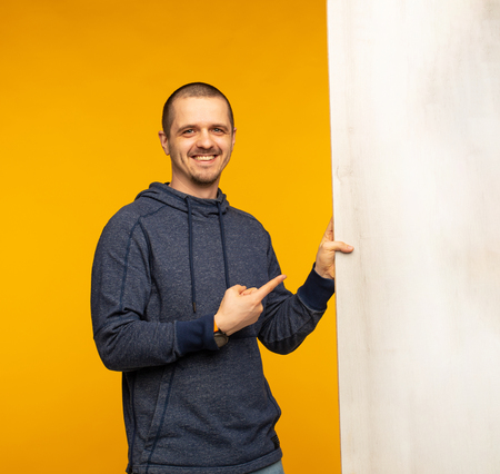 Man holding big white wooden banner and pointing on it Stock Photo