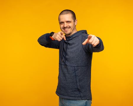 Man looking in camera and pointing by two hands