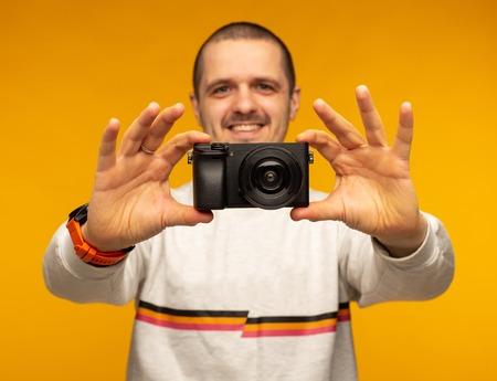 Man photographer holding mirrorless camera in both hands
