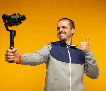 Man blogger making video and show thumbs up in camera Stock Photo