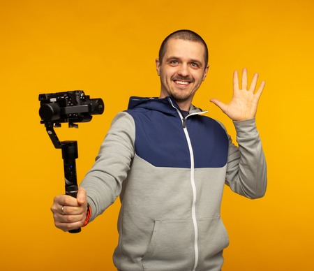 Man vlogger or video blogger holding camera on gimbal and smiling in camera Stock Photo