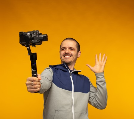 Man vlogger or blogger or videographer filming hisself on camera Stock Photo