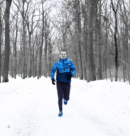 Man runner running in winter forest weared in blue jacket