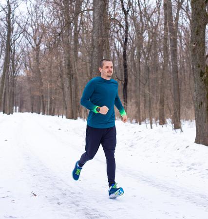 Man in blue sports wear running in forest