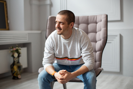 Man sitting on chair and looking on side Stock Photo
