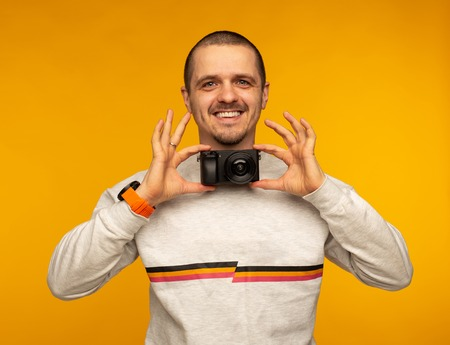Man photographer holding camera as bowtie and smiling
