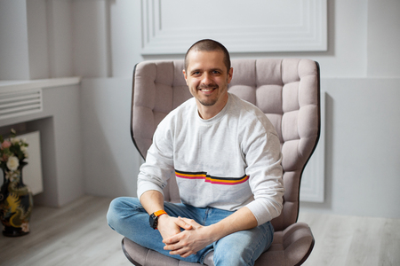 Man sitting on chair and smiling lookin in camera Stock Photo
