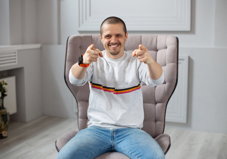 Smiling man pointing by two hands in camera