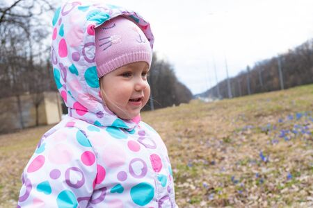 Girl and some first blue snowdrop flowers behind Stok Fotoğraf