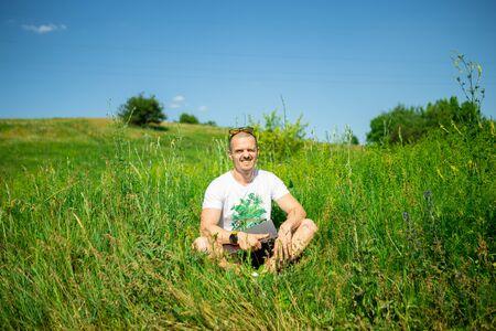 Man freelancer sitting on grass with laptop Zdjęcie Seryjne