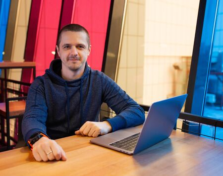 Man in hoodie sitting at desk with laptop