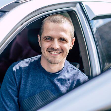 Smiling man looking in camera through car window