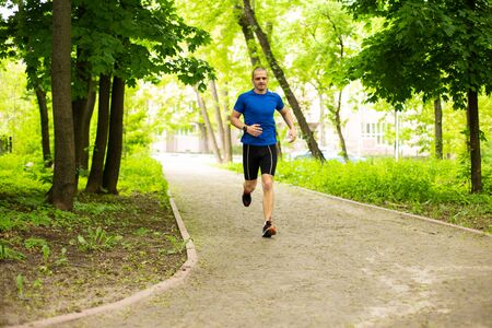 Man in blue tshirt run in the forest or park