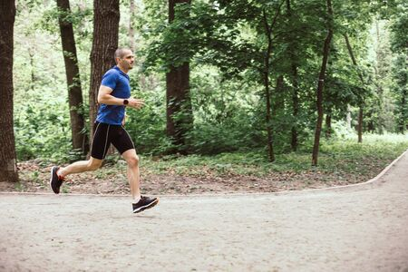 Man training and running in the forest or urban park
