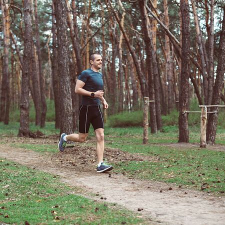 Athlete run in the pine summer forest