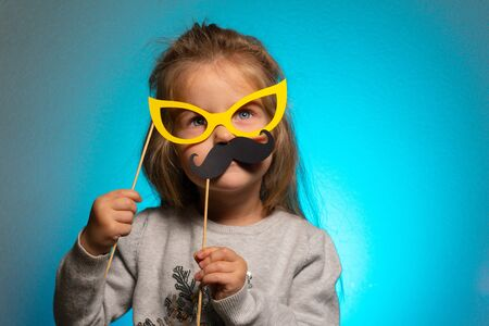 Little funny girl with mustaches and paper glasses