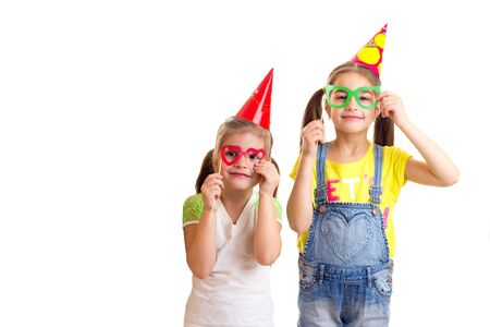 Couple of funny girl friends with party decorations looking in camera