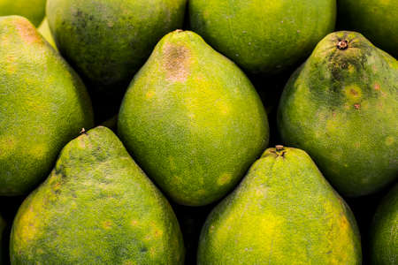 Imperfect pomelos stacked in a pile Stock Photo