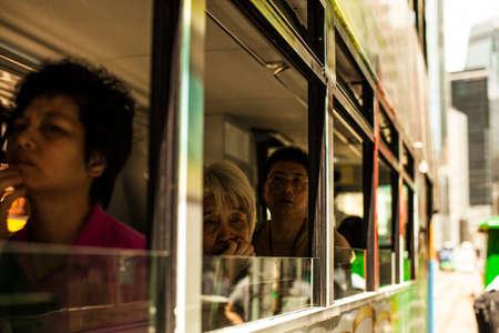 Hong Kong, China - 7 July, 2013: Passenger on the lower deck of a double decker tram in Causeway Bay district in Hong Kong Redactioneel