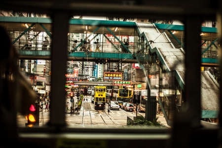 Hong Kong, China - 7 July, 2013: Looking down a street in Causeway Bay district with double deck trams, overhead walkways and buses