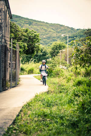 road cycling: Hong Kong, China - 23 May, 2009: Remote village with children cycling down a path on Lantau Island, town of Mui Wo