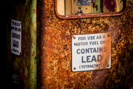 Abandoned gas pump with a rust and signs Stock Photo