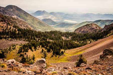 Looking down into a lush green mountain valley and flat land beyond in Flagstaff, Arizona Stock Photo - 77481239