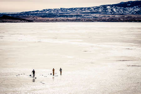 freshwater fish: Ice fishing on a frozen reservoir in Wyoming Stock Photo
