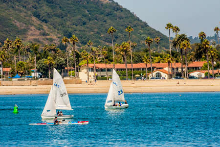 Santa Barbara, California - 8 August, 2008: Sailboats and a kayak in the water just off of the main beach with palm trees and a mountain in the background