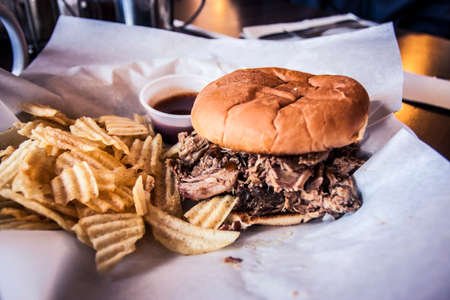 Pulled pork sandwich with a side of chips Stock Photo
