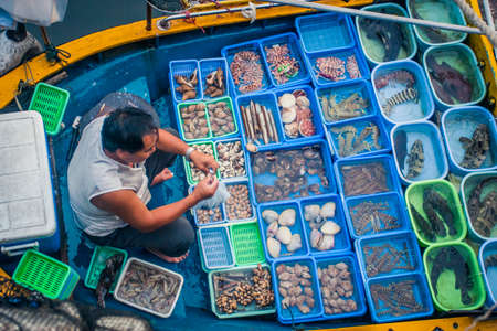 Hong Kong, China - 12 June, 2009: Local fisherman selling freshly caught seafood at the pier in Sai Kung Stock Photo